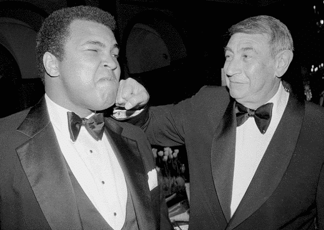 Howard Cosell is pretending to punch Muhammad Ali in the face while both wearing black tuxedo suits.