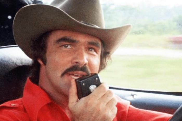 Burt Reynolds is talking on 10 meter radio wearing brown cowboy head in his car.